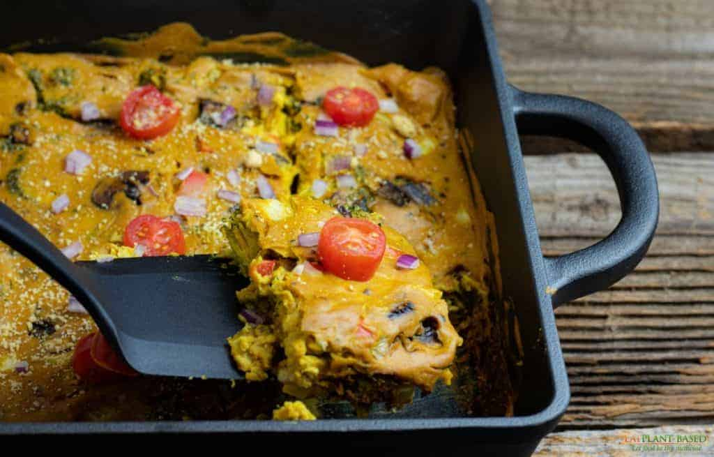 Vegan quiche casserole in cast iron pan with spatula lifting a slice