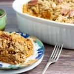 vegan casserole on plates and white wooden table with casserole dish in background and green coffee cup
