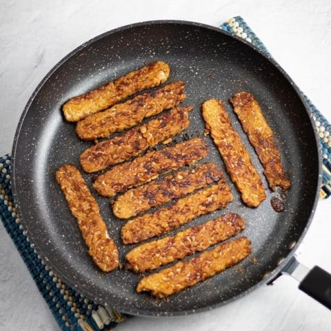 overhead photo of tempeh bacon in nonstick skillet on white background