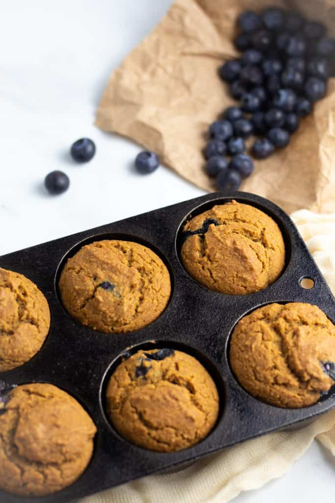 vegan blueberry muffins in cast iron muffin pan with blueberries in background