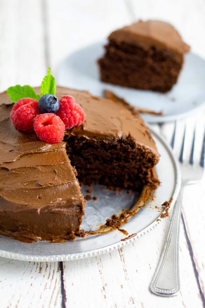 healthy chocolate cake with slice missing on silver plate topped with berries