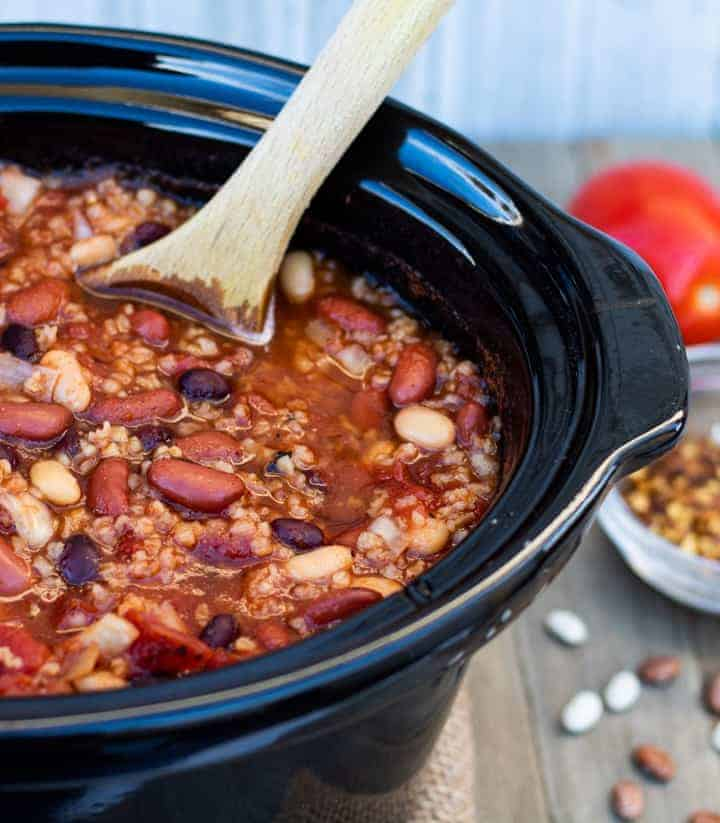 vegan crockpot chili in crock with wooden spoon