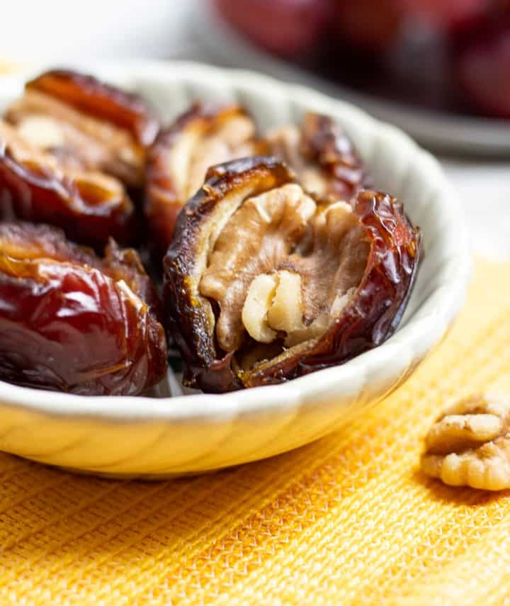 walnut stuffed dates in white dish with yellow napkin