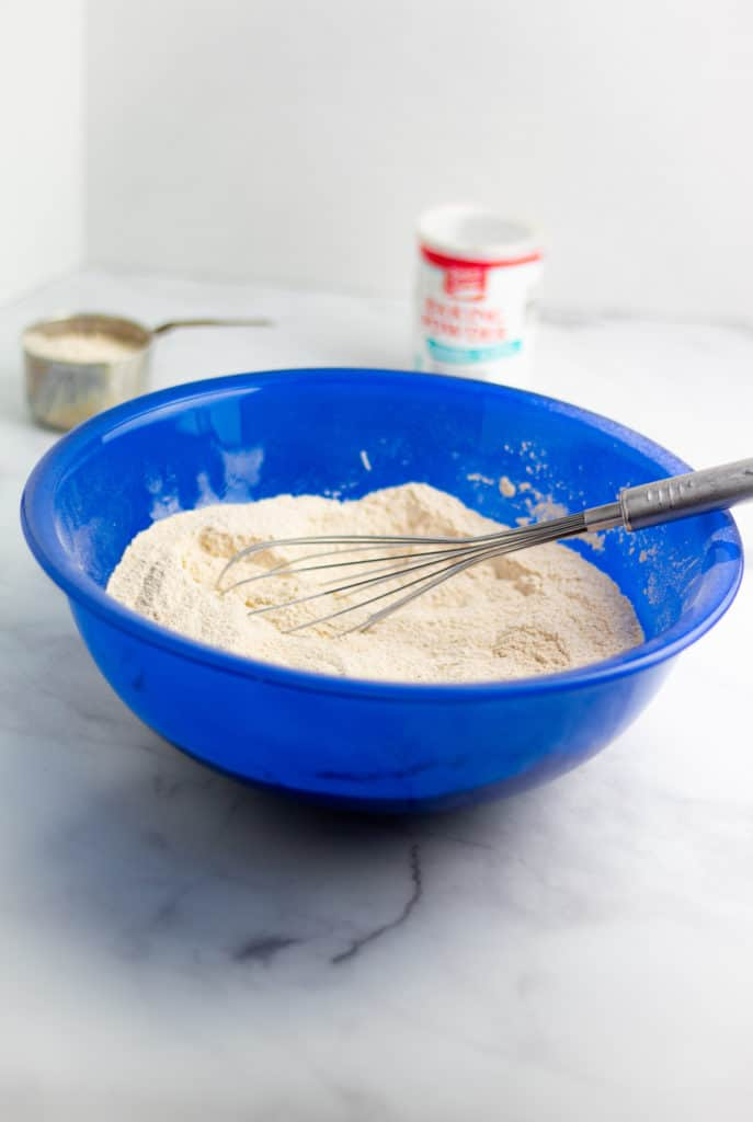 flour and dry ingredients for muffins in large blue bowl with whisk