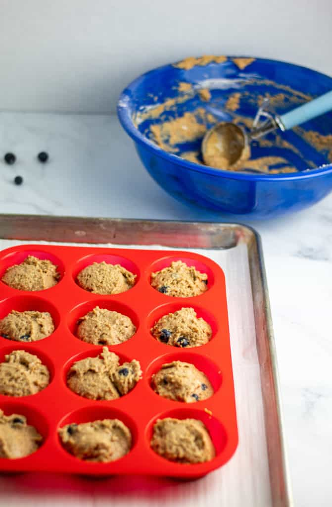 muffins in red silicone non stick baking pan with batter bowl in background