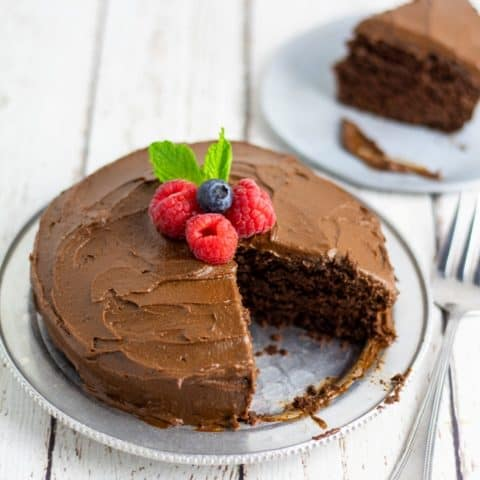 vegan chocolate sugar free cake on silver plate with one slice out