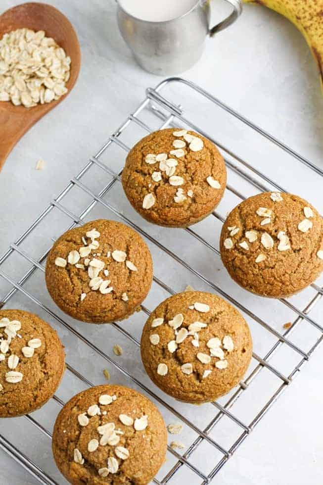 vegan muffins on cooling rack with oats sprinkled over the top on white background