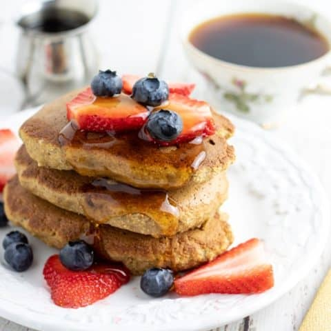 Banana oatmeal pancakes topped with blueberries and strawberries on white plate