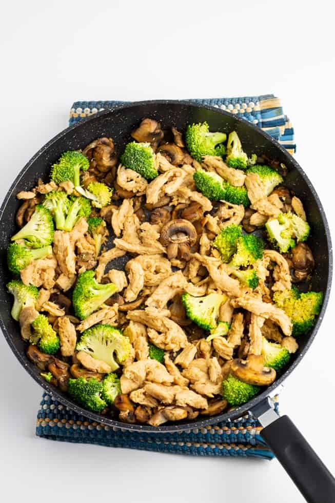 sauteed mushrooms and broccoli in pan white background