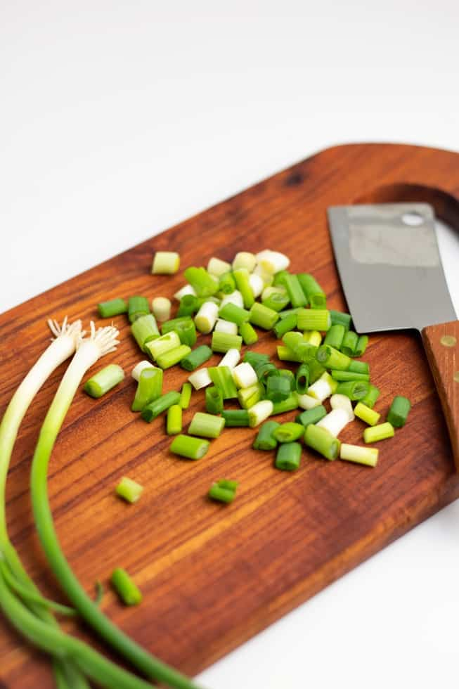 diced green onions on wooden cutting board