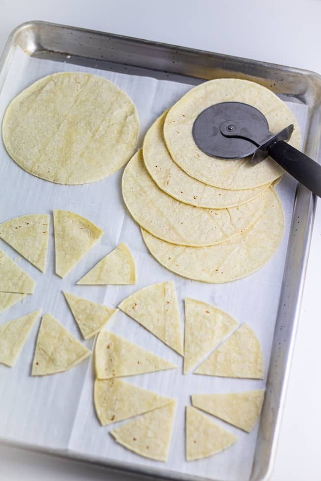 corn tortillas begin sliced with pizza cutter to make baked tortilla chips on baking sheet