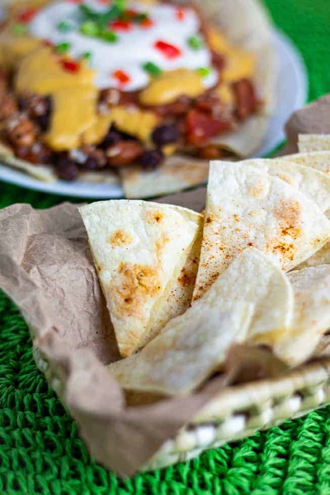 homemade tortilla chips in basket with nachos in background