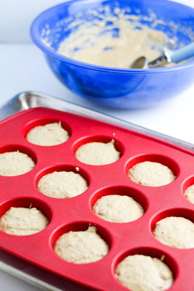 vegan muffin batter in red silicone muffin pan on white background