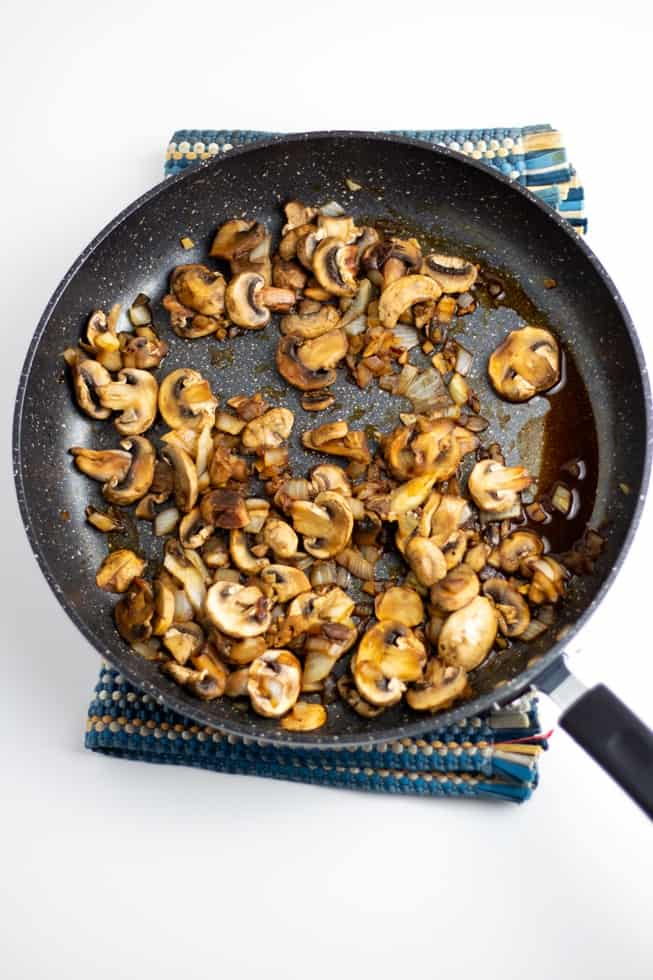 sauteed mushrooms and onions in pan white background