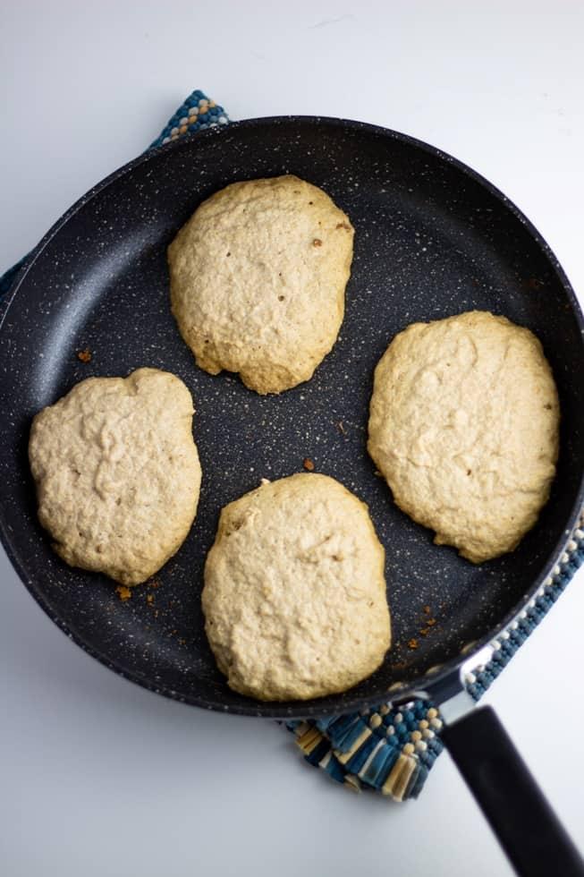 banana oat pancakes in nonstick pan