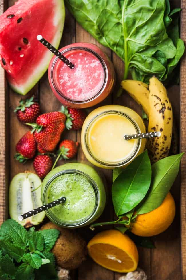 vegetable fruit smoothies in three mason jars with straws surrounded by produce