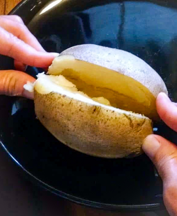 baked potato being sliced and opened