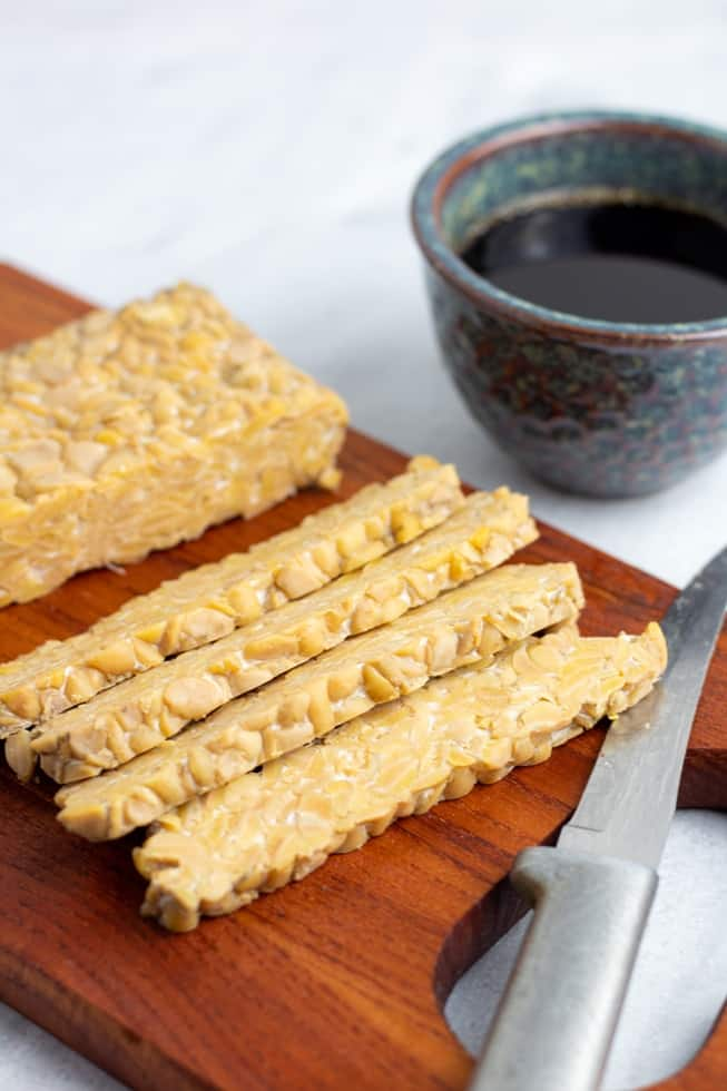 Sliced tempeh on wooden board with cup of marinade in background