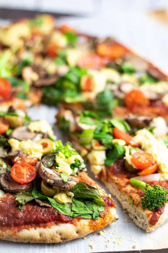 vegan pizza topped with veggies with slice out on white background