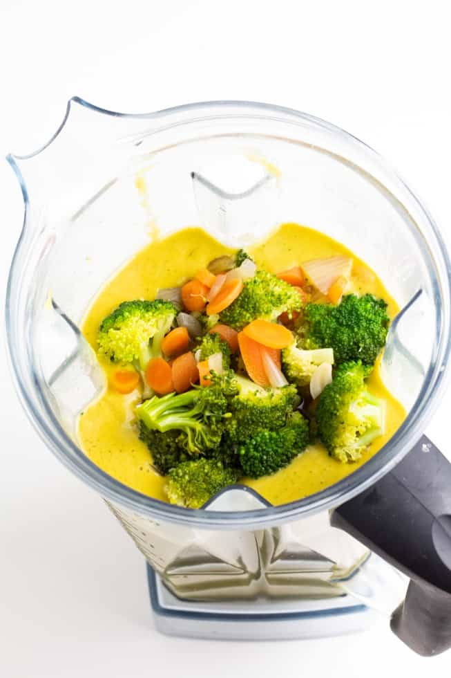 vegan cheese broccoli and carrots in vitamix on white background