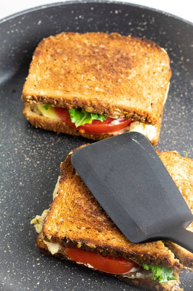 grilled cheese sandwich in nonstick pan with black spatula