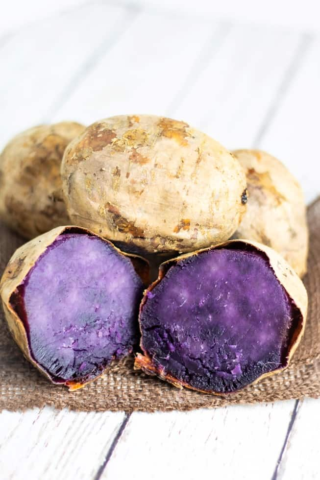 purple potato sliced in half surrounded by other whole potatoes on burlap