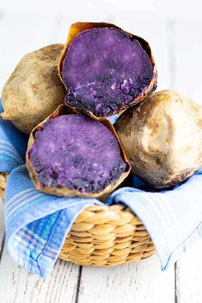 purple potato sliced in half in a basket with other potatoes