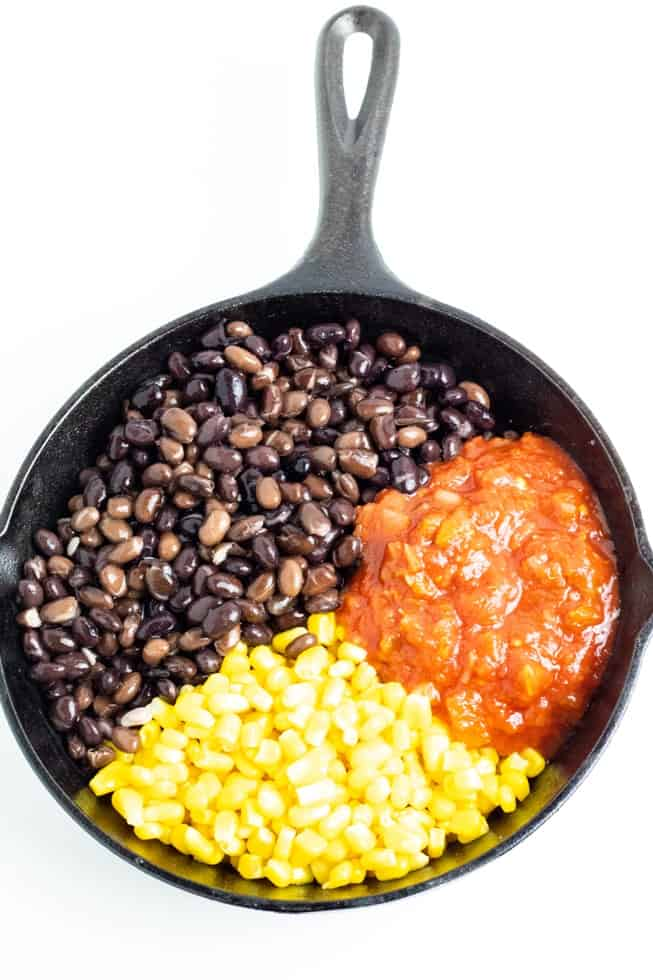 beans corn salsa in black cast iron pan on white background