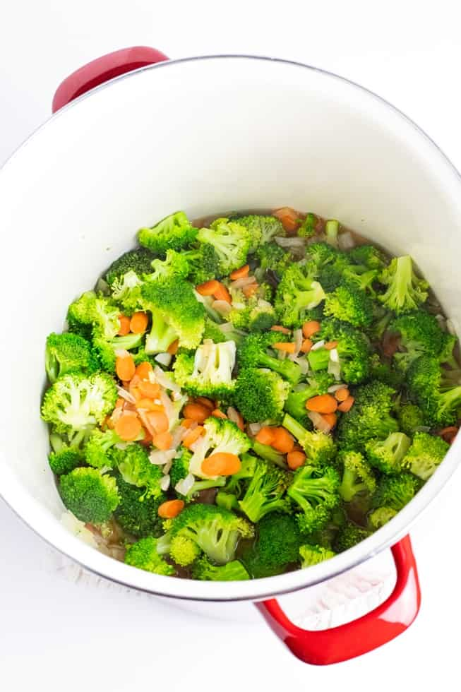 broccoli and carrots in red pot on white background