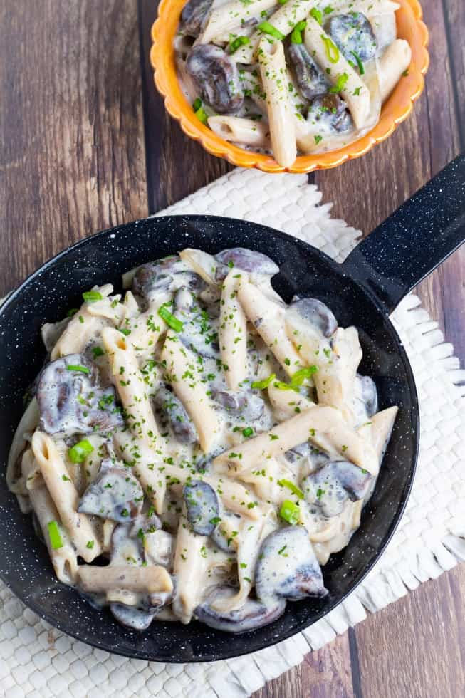 vegan stroganoff in dark metal pan on wooden table