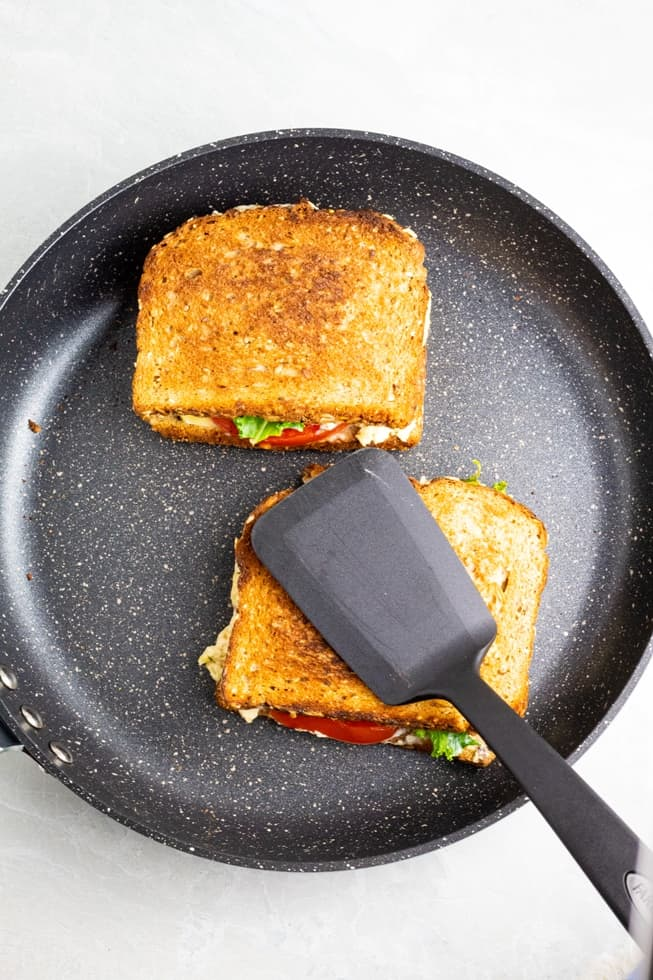 grilled cheese sandwiches in nonstick pan with black spatula