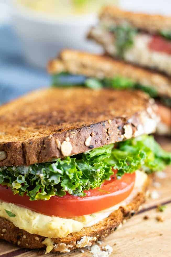 vegan grill cheese sandwich with tomato and kale on wooden board