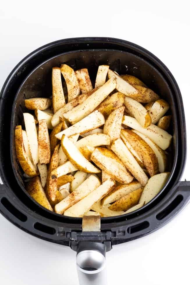 sliced potatoes in air fryer before cooked white background