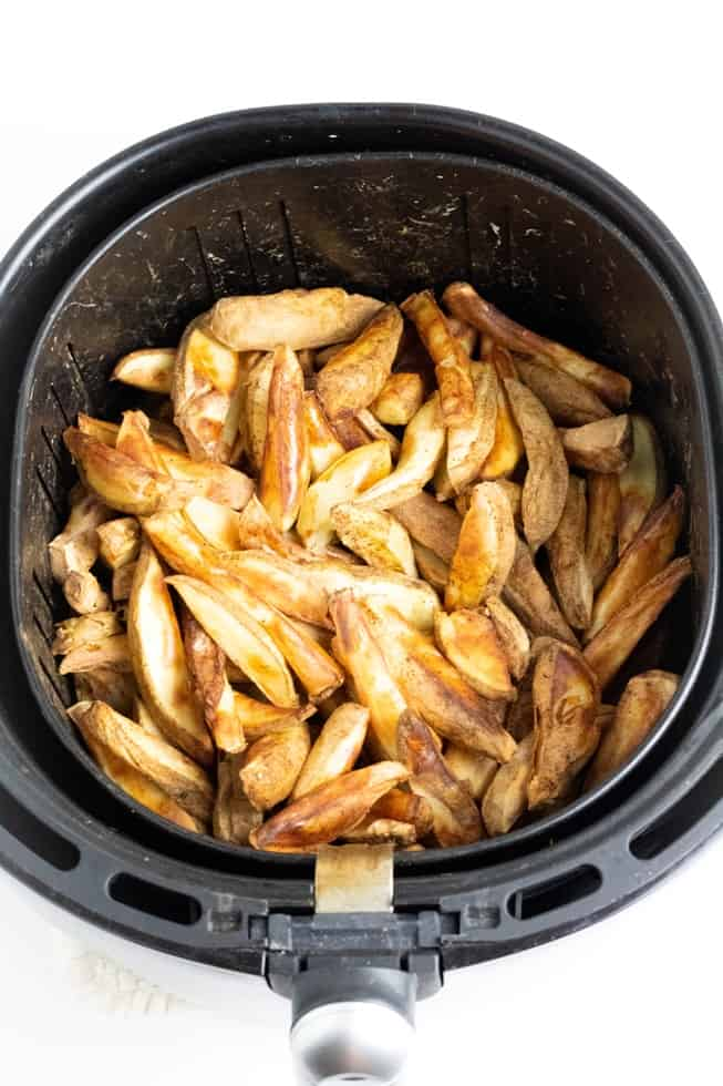 cooked french fries in air fryer on white background