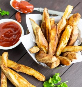 oil free french fries in basket with ketchup on wooden table