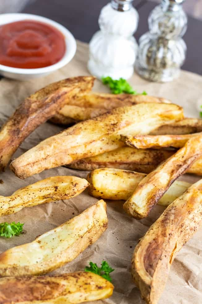air fryer french fries on brown bag with ketchup in background