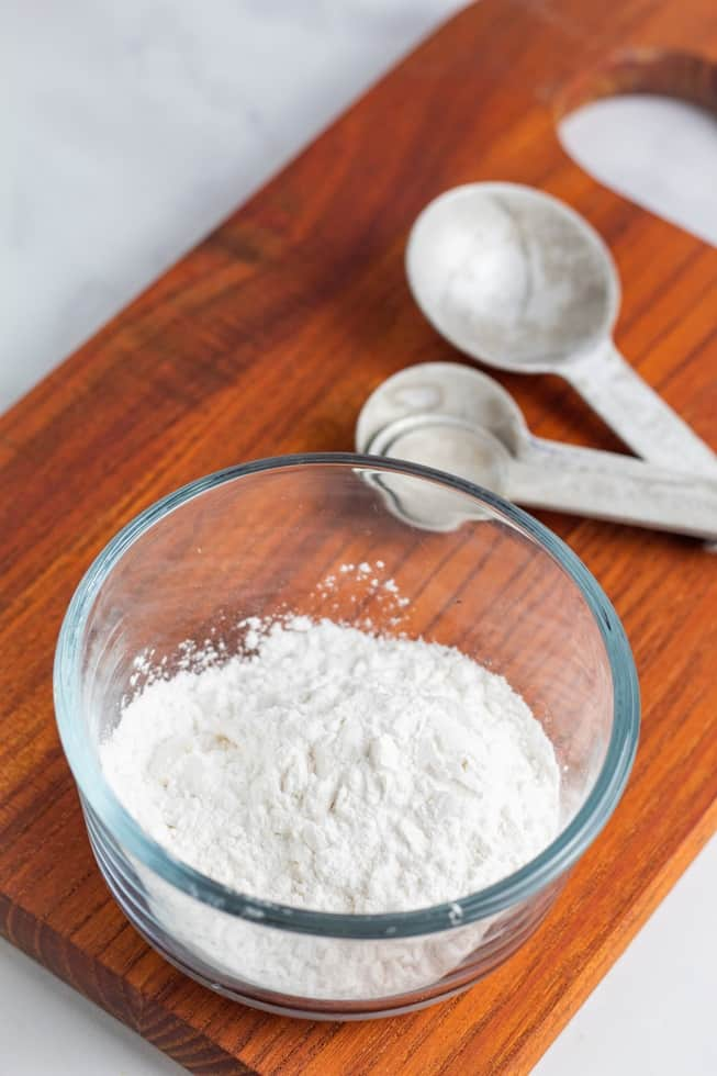 arrowroot powder in clear bowl on cutting board with measuring spoons