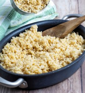 cooked bulgur in pan on wooden table