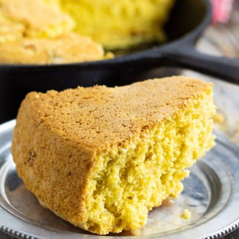 vegan cornbread slice on silver plate with cast iron pan in background