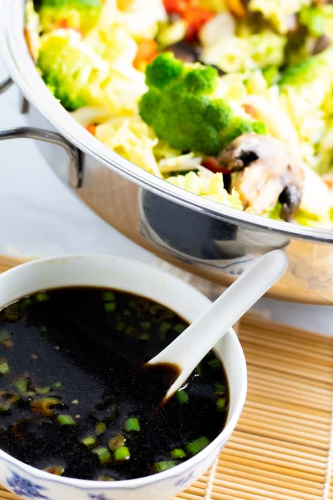 asian stir fry sauce in bowl on bamboo mat with white spoon and stir fry in pan