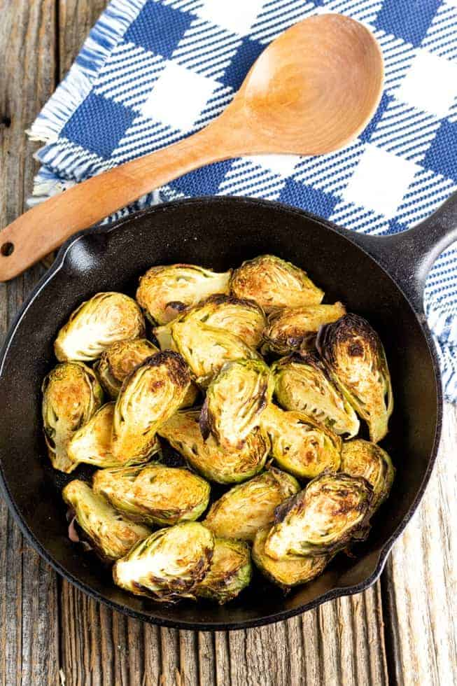 sliced brussels sprouts in cast iron pan on wooden table
