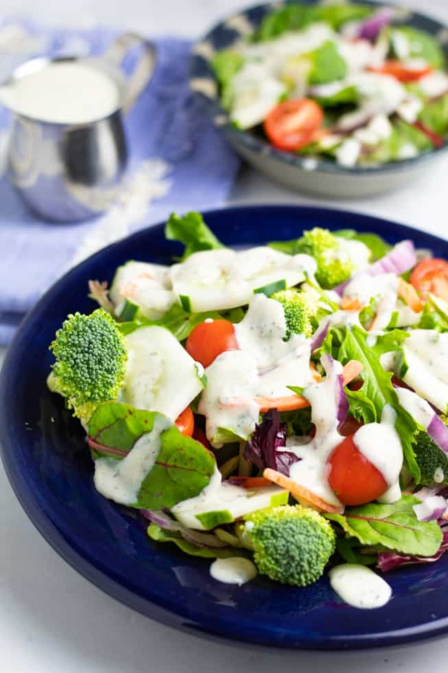 garden salad on blue plate with ranch dressing