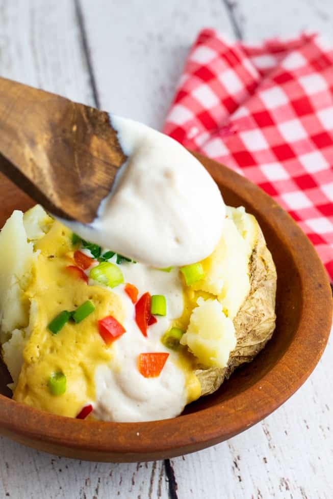 loaded baked potato with sour cream begin scooped onto it with wooden spoon