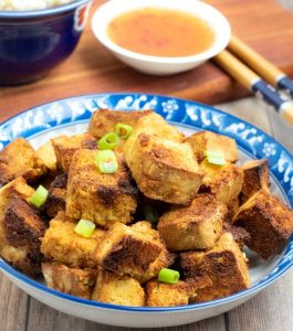 air frier tofu on blue asian bowl with chopsticks and dipping sauce in background