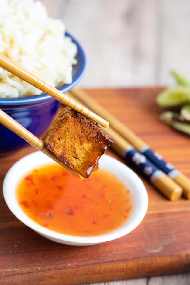 air fried tofu held in chopsticks over dipping sauce