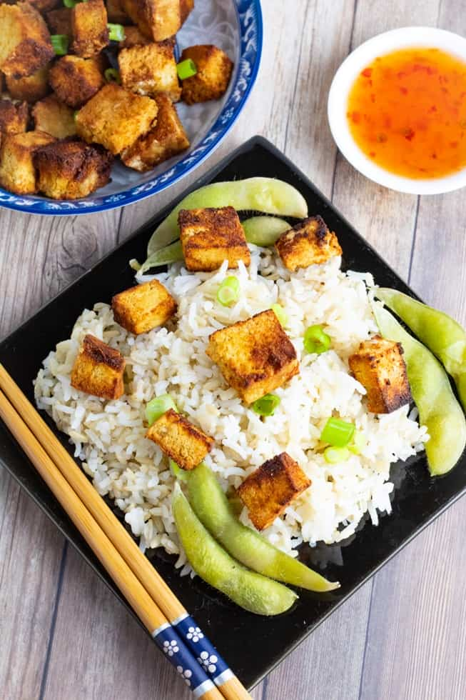 black square plate with steamed rice and tofu overhead shot