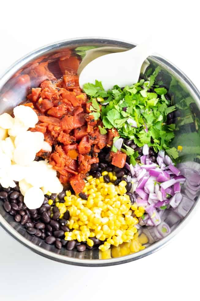 beans, corn, onion, cilantro, tomatoes, chestnuts in large stainless steel bowl on white background
