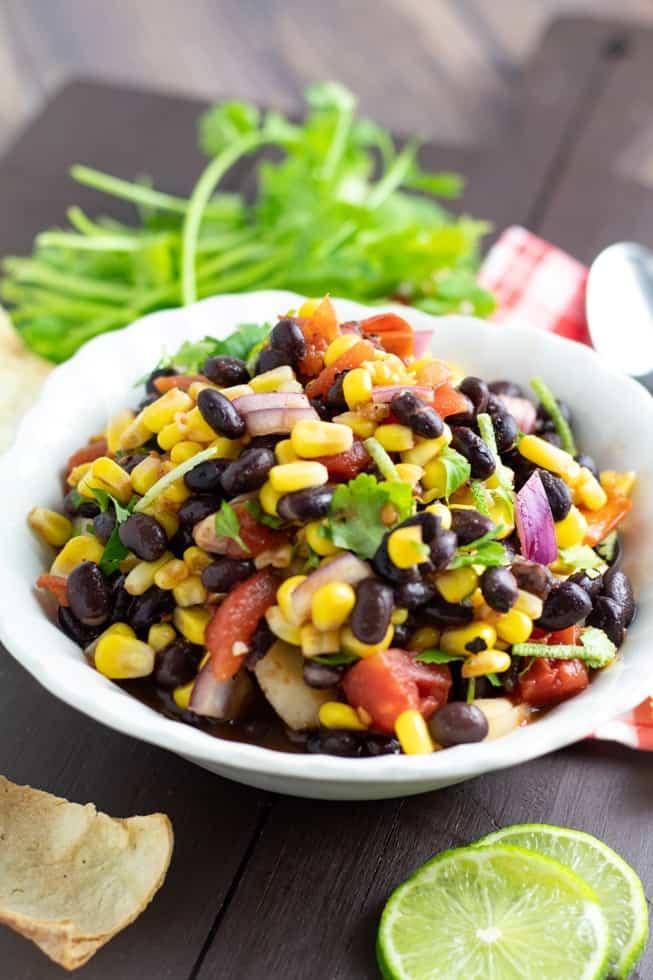 black bean corn salad in white bowl with cilantro in background