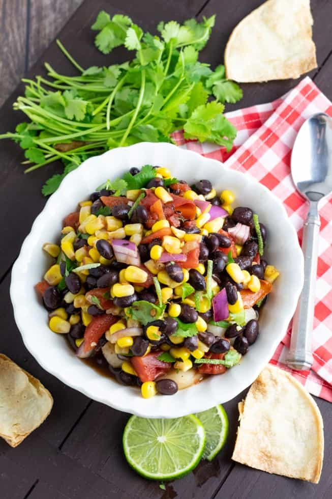overhead of white bowl full of bean salad on dark wood table