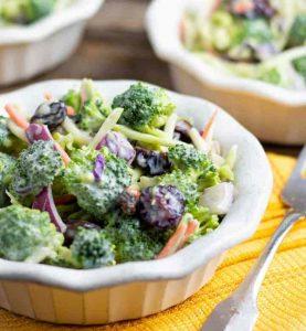 broccoli salad in white bowl on yellow napkin